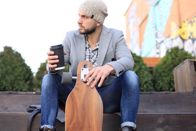 Jovem bonito no casaco cinza e chapéu, descansando, sentado com longboard, bebendo café. conceito de skate urbano.