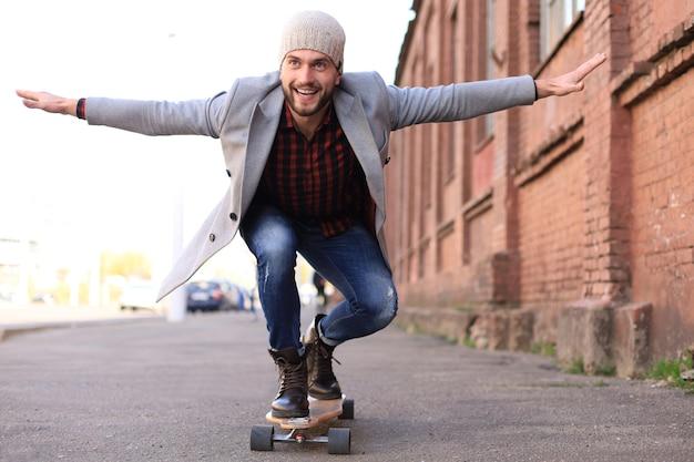 Jovem bonito no casaco cinza e chapéu no longboard na rua da cidade. conceito de skate urbano.