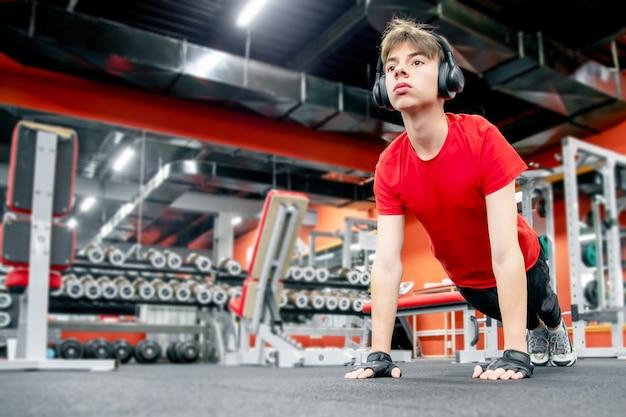Jovem bonito no sportswear e fones de ouvido fazendo flexões no ginásio