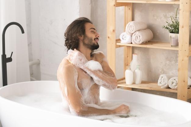 Jovem bonito nu sentado na banheira com água quente e espuma, lavando o corpo e apreciando o procedimento