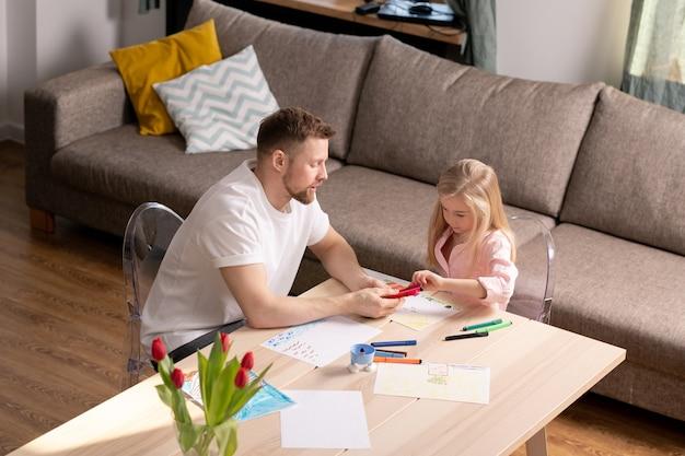 Jovem bonito oferecendo sua filhinha para escolher giz de cera antes de desenhar no papel, enquanto os dois estão sentados à mesa