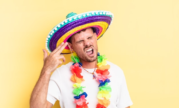 Jovem bonito olhando infeliz e estressado, gesto de suicídio fazendo sinal de arma. conceito de festa mexicana