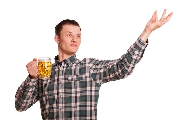 Jovem bonito olhando longe posando com um copo de cerveja, copie o espaço ao lado. homem comemorando oktoberfest isolado no branco