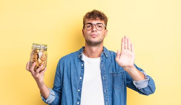 Jovem bonito olhando sério mostrando a palma da mão aberta, fazendo gesto de parada. conceito de garrafa de biscoitos