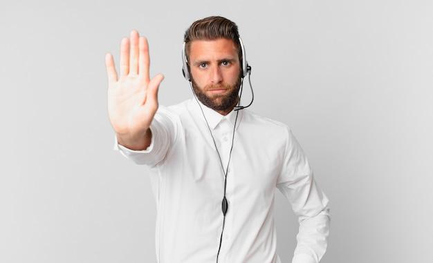 Jovem bonito olhando sério mostrando a palma da mão aberta, fazendo gesto de parada. conceito de telemarketing