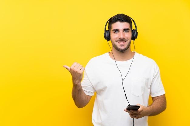 Jovem bonito ouvindo música com um celular sobre parede amarela isolada, apontando para o lado para apresentar um produto