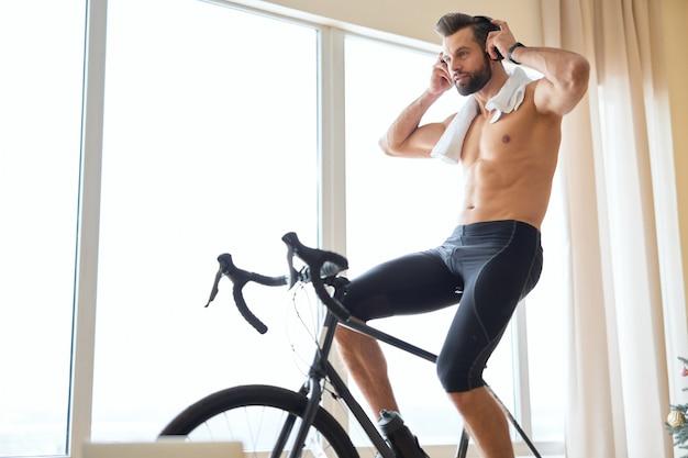 Jovem bonito ouvindo música e andando de bicicleta papelaria