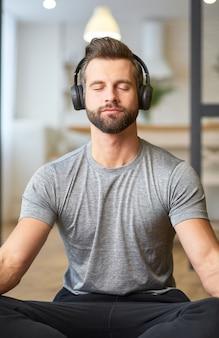 Jovem bonito ouvindo música e meditando
