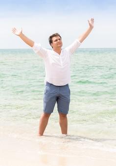Jovem bonito parado com as mãos levantadas na praia e olhando para o céu
