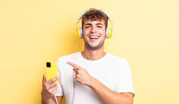 Jovem bonito parecendo animado e surpreso, apontando para o lado. conceito de fones de ouvido e smartphone