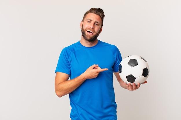 Jovem bonito parecendo animado e surpreso, apontando para o lado. conceito de futebol
