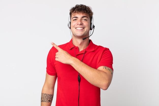 Jovem bonito parecendo animado e surpreso, apontando para o lado. conceito de telemarketing
