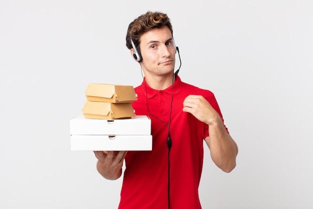 Jovem bonito parecendo arrogante, bem sucedido, positivo e orgulhoso. conceito de comida rápida para viagem