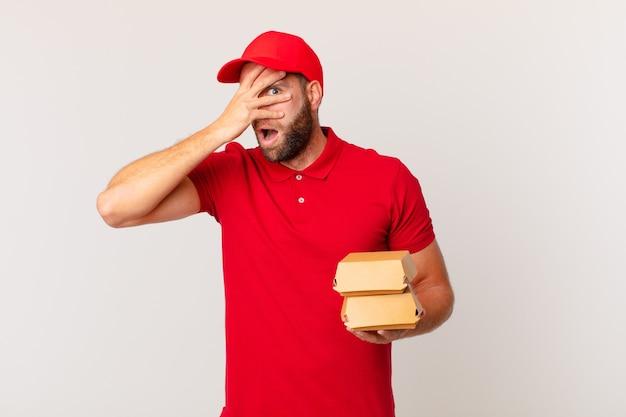 Jovem bonito parecendo chocado, assustado ou apavorado, cobrindo o rosto com um conceito de entrega de hambúrguer à mão