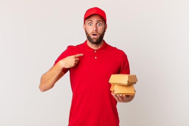 Jovem bonito parecendo chocado e surpreso com a boca aberta, apontando para o conceito de entrega de hambúrguer self