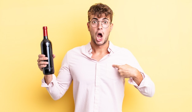 Jovem bonito parecendo chocado e surpreso com a boca aberta, apontando para si mesmo. conceito de garrafa de vinho