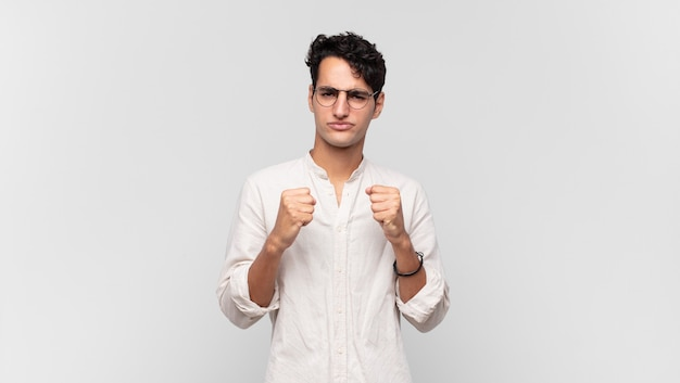 Jovem bonito parecendo confiante, zangado, forte e agressivo, com punhos prontos para lutar em posição de boxe