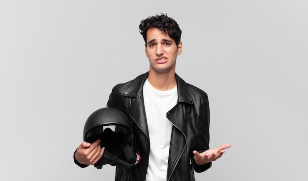 Jovem bonito parecendo desesperado e frustrado, estressado, infeliz e irritado, gritando e gritando. conceito de motociclista