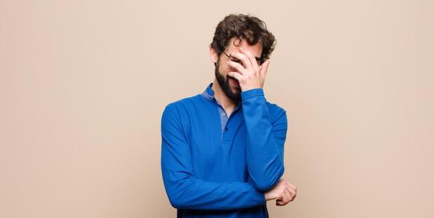 Jovem bonito parecendo estressado, envergonhado ou chateado, com dor de cabeça, cobrindo o rosto com a mão contra uma parede plana