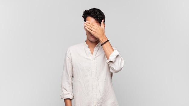 Jovem bonito parecendo estressado, envergonhado ou chateado, com dor de cabeça, cobrindo o rosto com a mão