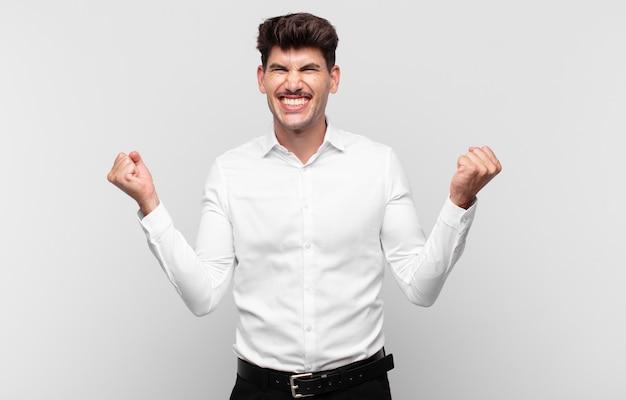 Jovem bonito parecendo extremamente feliz e surpreso, comemorando o sucesso, gritando e pulando