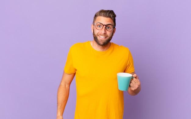 Jovem bonito parecendo feliz e agradavelmente surpreso. e segurando uma caneca de café