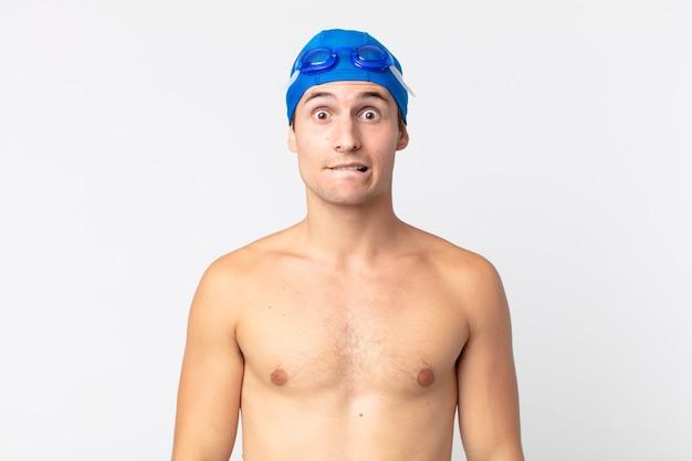 Jovem bonito parecendo perplexo e confuso. conceito de nadador