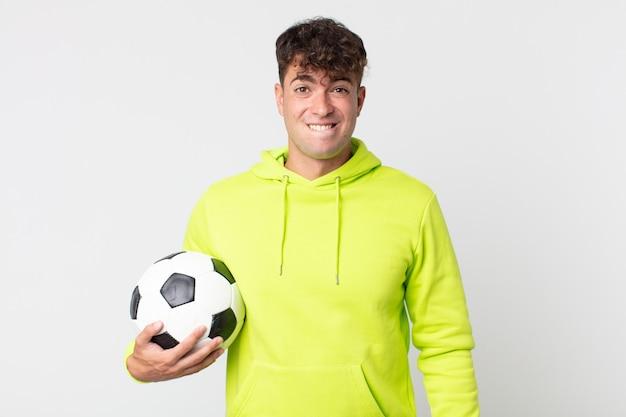 Jovem bonito parecendo perplexo e confuso segurando uma bola de futebol