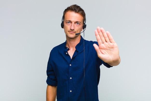 Jovem bonito parecendo sério, severo, descontente e irritado, mostrando a palma da mão aberta fazendo gesto de parada