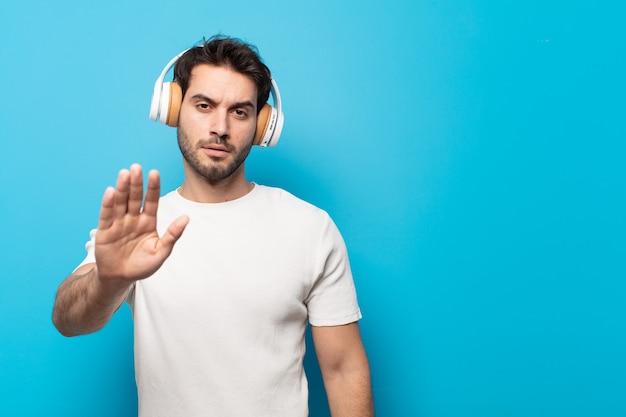 Jovem bonito parecendo sério, severo, descontente e irritado mostrando a palma da mão aberta fazendo gesto de parada