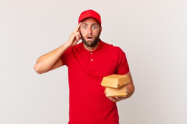 Jovem bonito parecendo surpreso ao perceber um novo conceito de entrega de hambúrguer de pensamento, ideia ou conceito