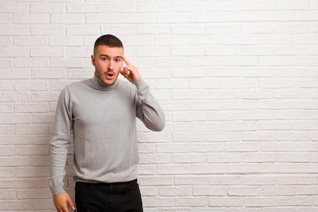 Jovem bonito parecendo surpreso, boquiaberto, chocado, percebendo um novo pensamento, ideia ou conceito contra uma parede plana