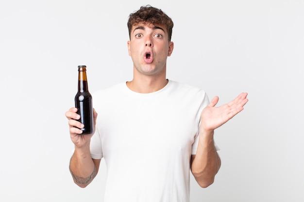 Jovem bonito parecendo surpreso e chocado, com o queixo caído segurando um objeto e segurando uma garrafa de cerveja