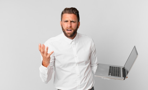 Jovem bonito parecendo zangado, irritado e frustrado, segurando um laptop