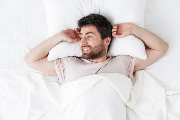 Jovem bonito pela manhã se espreguiçando na cama