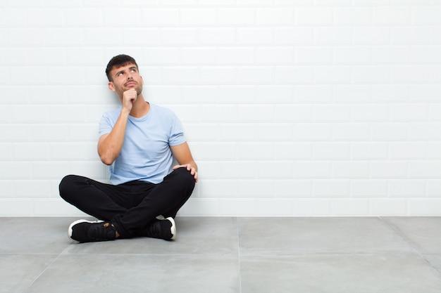 Jovem bonito pensando, sentindo-se duvidoso e confuso, com diferentes opções, imaginando qual decisão tomar sentado no chão de cimento