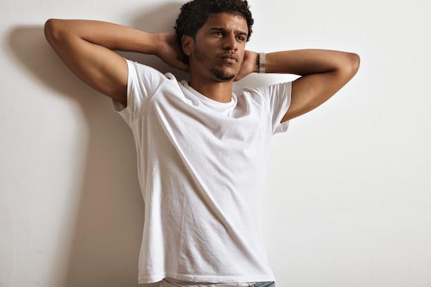 Jovem bonito pensativo e sonhador em uma camiseta branca lisa com as mãos atrás da cabeça na parede branca