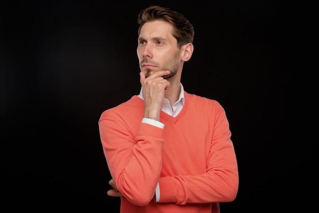 Jovem bonito pensativo em um suéter laranja esfregando o queixo enquanto pensava em uma estratégia, fundo preto