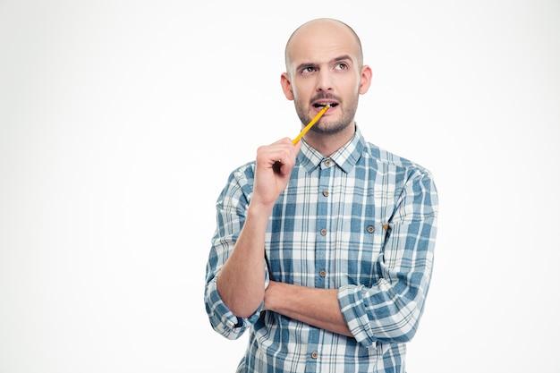 Jovem bonito pensativo em uma camisa xadrez com um lápis na boca isolado sobre uma parede branca