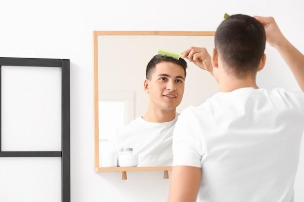 Jovem bonito penteando o cabelo em casa
