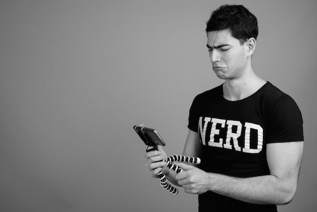 Jovem bonito persa nerd com óculos contra uma parede cinza em preto e branco