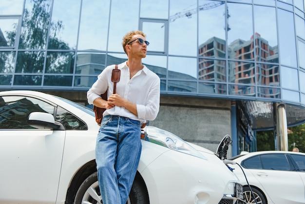 Jovem bonito perto de um carro elétrico moderno. o conceito de transporte ecológico.