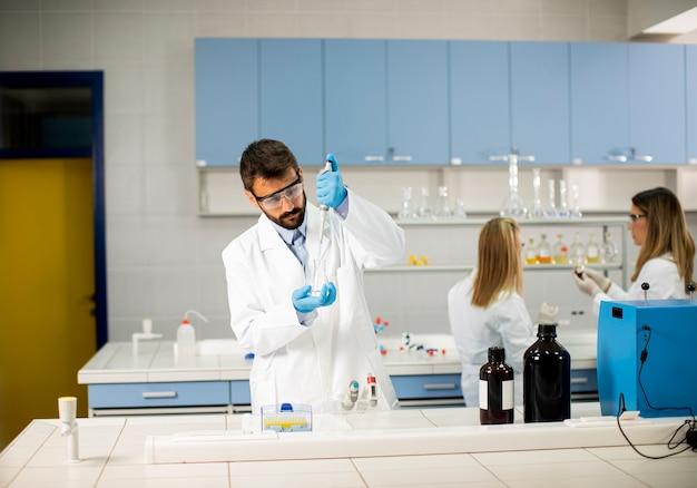Jovem bonito pesquisador em roupas de trabalho de proteção em pé no laboratório e analisando frasco com líquido