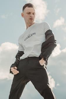 Jovem bonito posando em uma camiseta branca e um terno preto na frente do céu nublado.