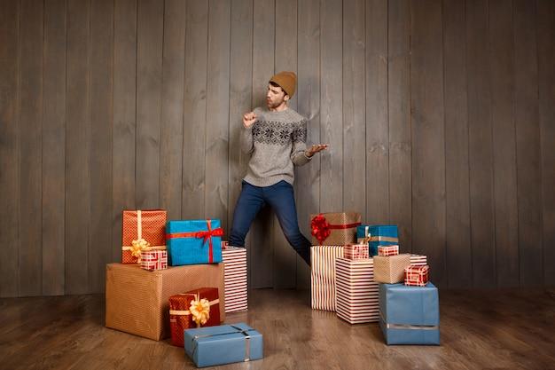 Jovem bonito posando entre presentes de natal por cima da parede de madeira