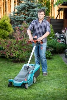 Jovem bonito posando no quintal com o cortador de grama