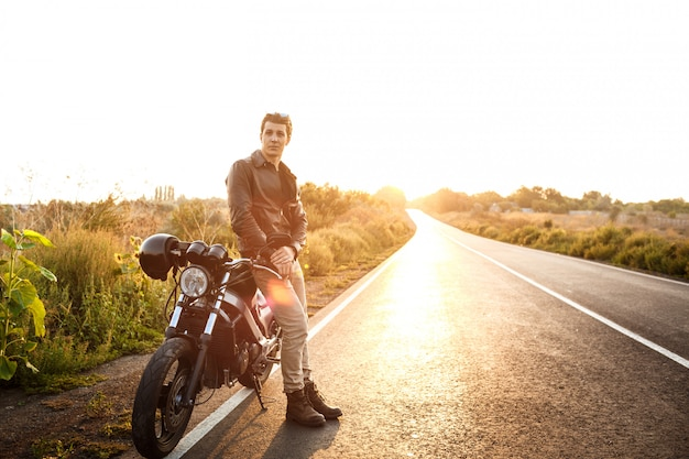 Jovem bonito posando perto de sua moto na estrada rural.