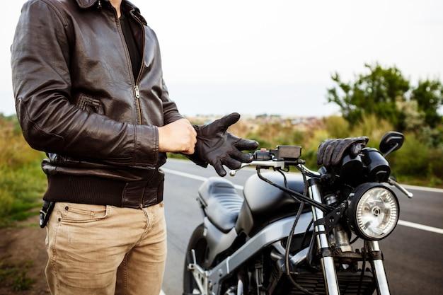 Jovem bonito posar perto de sua moto, usando luvas.