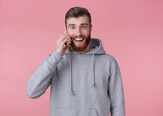 Jovem bonito positivo barbudo homem com capuz cinza, parece feliz e sorri amplamente, falando ao telefone com a namorada, fica sobre um fundo rosa.