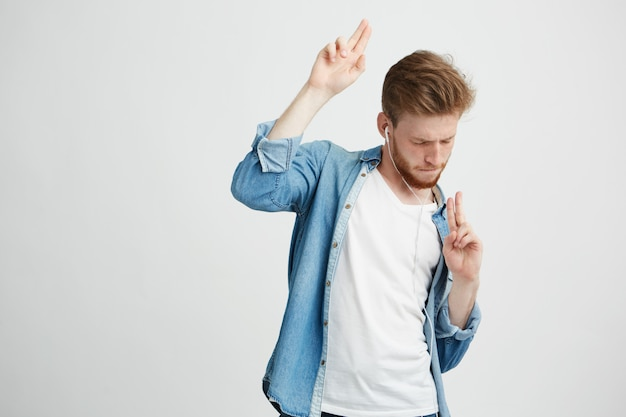 Jovem bonito positivo em fones de ouvido, ouvindo música dançando em movimento.